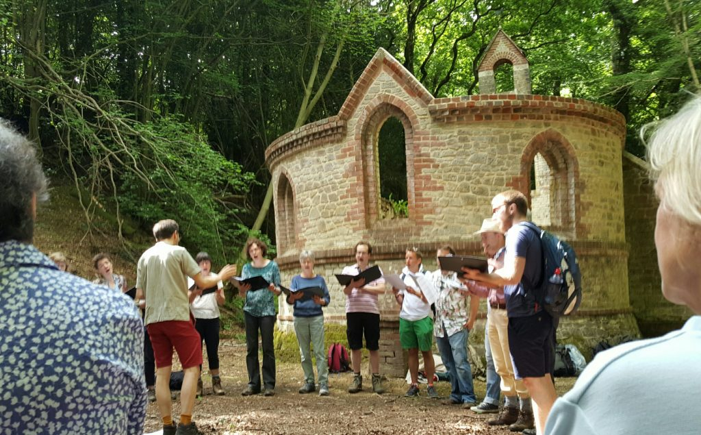 we see a small group of singers in front of old Bedham chapel in the woods.