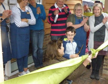 Image of people watching as the youngest member of the school cuts the ribbon to open the shop