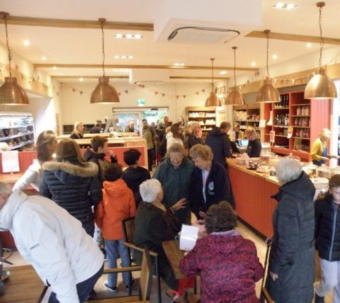 People are seen greeting each other in the shop